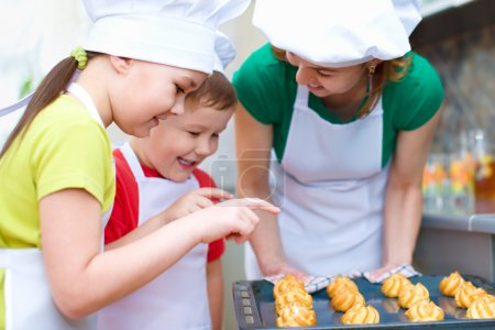 Photo for Mother with happy children making bread in the kitchen - Royalty Free Image