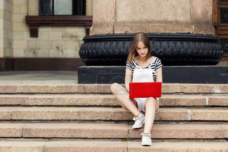 Young woman with laptop sitting on stairs near the university