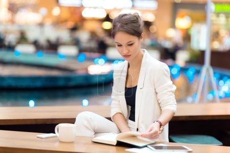 Photo pour Jeune, belle fille en costume blanc, assise dans le café à la réunion d'affaires - image libre de droit