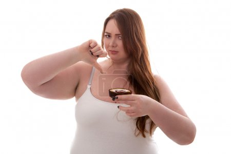 Beautiful plus size woman holding cake on her hand isolated on white background
