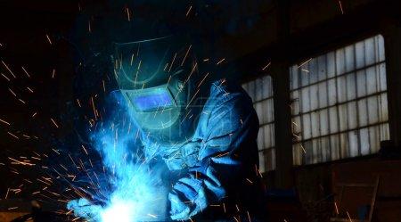 Photo pour Soudeurs travaillant à l'usine faites de métal de soudage soudage électrique. Aux travailleurs portant des unifrma et la protection pour Tovo à exécuter avec compétence les travaux - image libre de droit