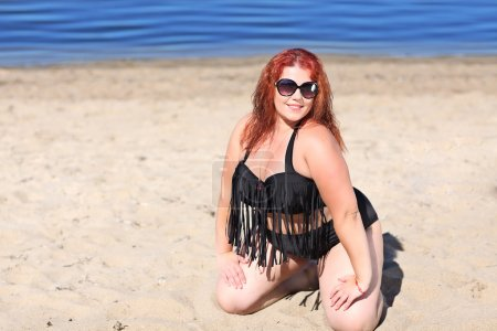 Redhead woman in sunglasses resting on beach