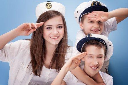 Photo pour Famille s'amuser, Frères et sœur portant le chapeau de capitaine. Fond bleu . - image libre de droit