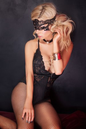 Photo for Sexy beautiful blonde woman posing in elegant black lingerie and mask. Perfect body. - Royalty Free Image