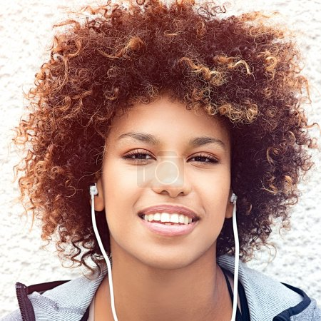 Photo for Photo of fit and sporty young woman listening to music . Beautiful african american girl with afro smiling. Outdoor shot. - Royalty Free Image
