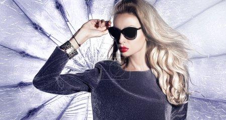 Photo pour Belle jeune femme blonde à la mode posant en studio portant des lunettes de soleil . - image libre de droit