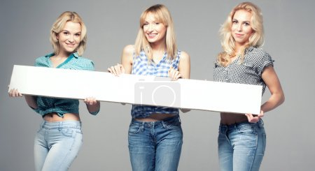 Photo for Three beautiful young woman posing in fashionable jeans, holding empty board. Blonde girls. Studio photo. - Royalty Free Image