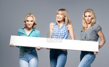 Photo for Three beautiful young woman posing in fashionable jeans, looking at camera. Blonde girls. Studio photo. - Royalty Free Image