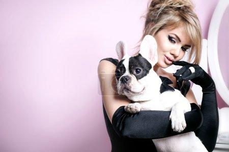 Elegant blonde woman posing with pug dog.