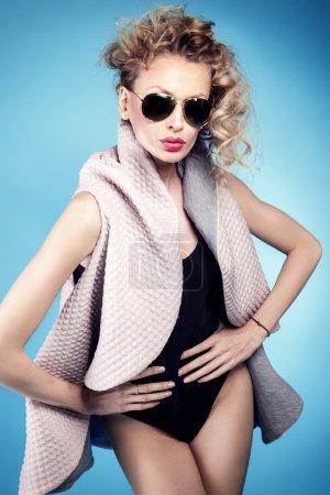 Photo pour Femme blonde à la mode posant sur fond bleu, portant des lunettes de soleil . - image libre de droit