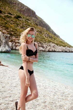 Photo for Smiling happy blonde woman relaxing on the beach, wearing fashionable sunglasses. Summer photo. - Royalty Free Image