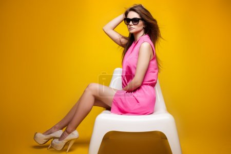 Photo for Fashionable photo of young beautiful romantic woman with long healthy hair and perfect makeup. Girl wearing pink dress. Studio shoot. Summer, spring style. Yellow background. - Royalty Free Image