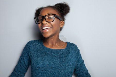 Photo pour Portrait de heureuse belle jeune fille africaine avec le sourire de dents. Adolescente posant en studio, portant des lunettes à la mode . - image libre de droit