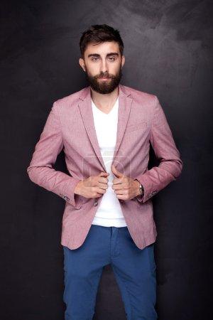 Photo pour Elégant jeune homme beau posant en studio, regardant la caméra. Homme barbu . - image libre de droit
