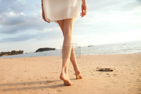 Woman legs on the beach.