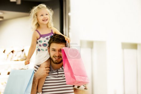 Photo for Happy family in shopping mall. Daughter is enjoying on father's shoulders. - Royalty Free Image