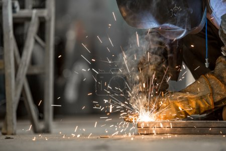 Photo pour Homme travaillant sur le sol, soudure, avec masque et gants pour la protection. Travail manuel . - image libre de droit