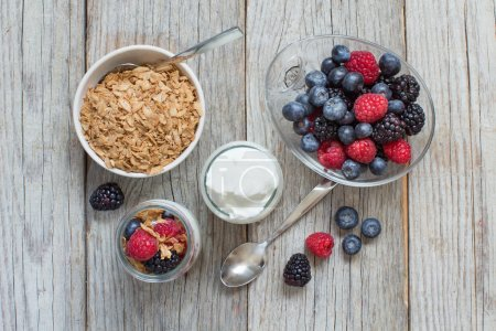 Photo for Healthy breakfast with Fresh greek yogurt, flakes  and berries on wood - Royalty Free Image
