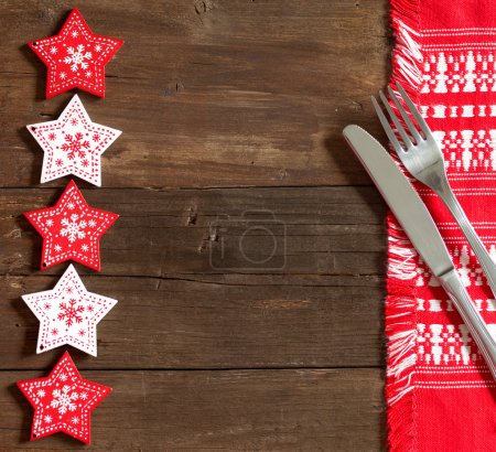 Photo pour Fond de table de Noël avec des étoiles rouges, serviette de table rouge, fourchette et couteau - image libre de droit