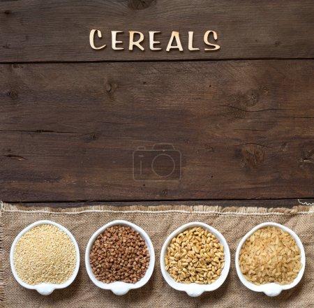 Photo pour Céréales dans des bols bordure avec mot Céréales sur bois - image libre de droit