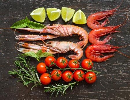 Photo pour Langoustines crues et crevettes aux légumes sur le bois sombre - image libre de droit