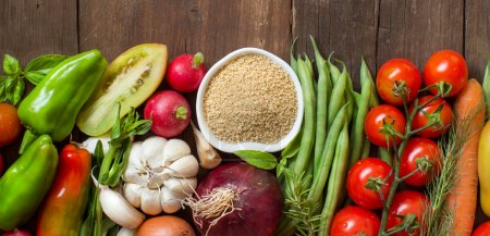 Photo for CousCous in a bowl and fresh vegetables on wood - Royalty Free Image