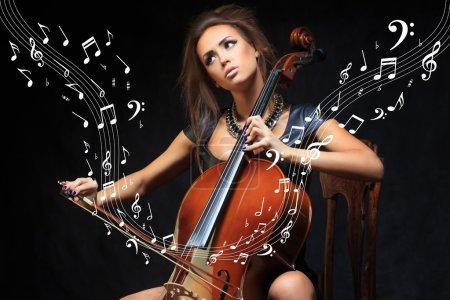 Photo pour Jolie jeune femme musicien jouant du violoncelle lors d'un récital classique, se concentrant sur ses notes dans l'obscurité, bouchent la vue - image libre de droit
