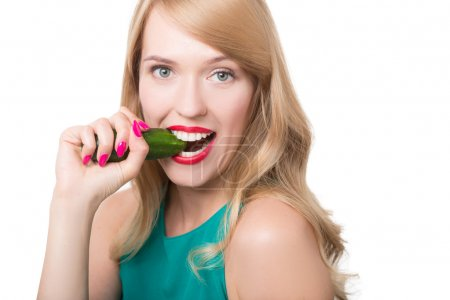 Young woman eating cucumber.