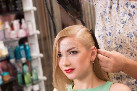 Photo pour Coiffeur fait coiffure pour belle fille dans le salon de coiffure - image libre de droit