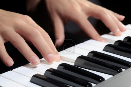 Girls hands on the keyboard of the piano