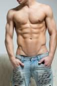 Svalnatý muž v roztrhané džíny stojí poblíž pohovka
