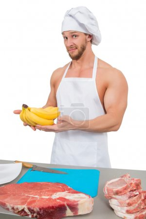 Photo for Bodybuilder chef in a white apron holding bananas - Royalty Free Image