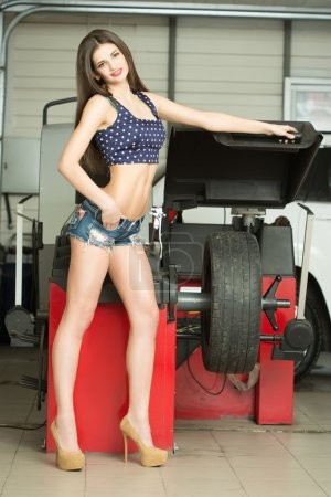 girl mechanic replace tires on wheels