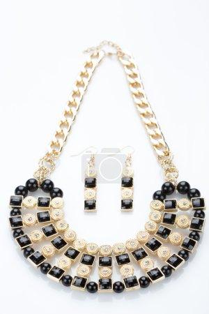metal feminine necklace. on white background. earrings