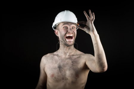 Happy dirty worker in helmet. gemstone, smiling an...