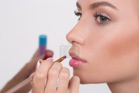 Makeup artist applies lipstick. Beautiful woman face.