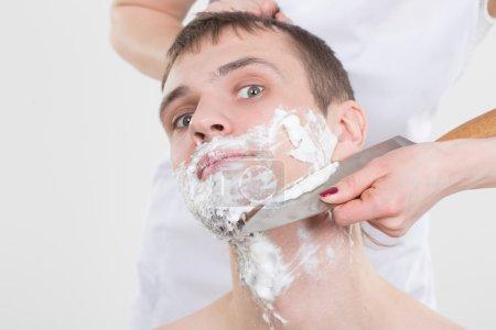 Photo pour Jeune bel homme rase une femme avec un couteau - image libre de droit