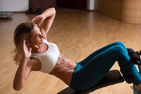 Photo pour Belle jeune femme en vêtements de sport formant ses abdos. appareils de formation - image libre de droit