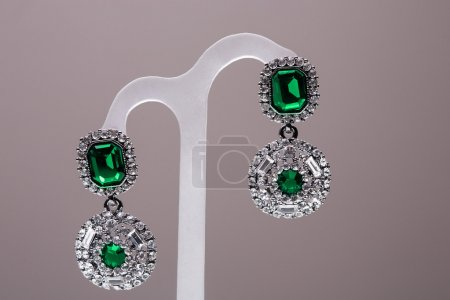 Earrings with green stones on the gray