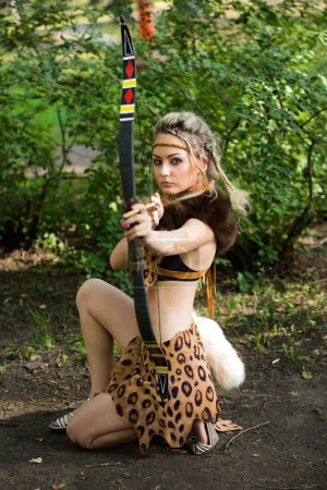 amazon woman posing with bow in green forest