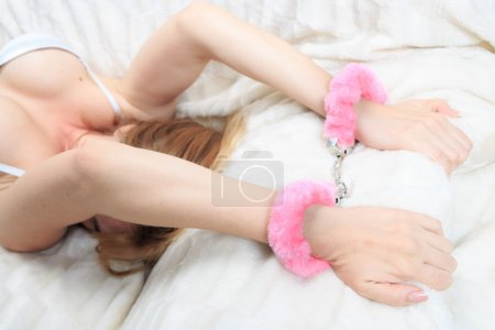 female hands in pink fur handcuffs. on the background sheet. sex toys.