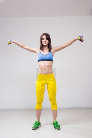 Photo pour Femme sportive souriante pompant les muscles avec des haltères - image libre de droit