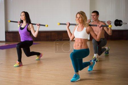 Photo pour Concept de fitness, de sport, d'entraînement, de gymnastique et de style de vie - groupe de personnes souriantes s'entraînant avec des cloches dans la salle de gym - image libre de droit