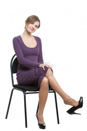 woman sits a chair. pose showing sexual desire. flirting. legs crossed, shoe drops. flexing. Isolated white background. body language