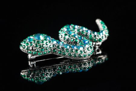 brooch in the form of a snake. green stones. black background
