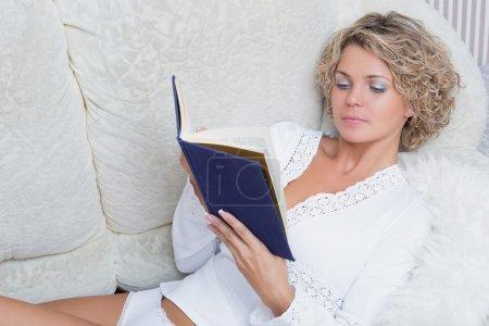 Photo pour Sexy blonde fille lecture un livre couché sur un canapé - image libre de droit