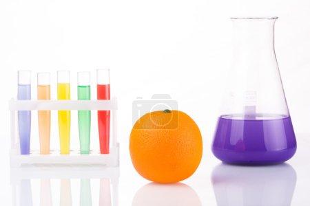Photo pour Tubes à essai chimiques à proximité des fruits. Génie génétique. pesticides dans les aliments. Fond blanc - image libre de droit