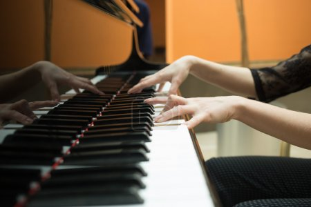 Womens hands on the keyboard of piano. girl plays music