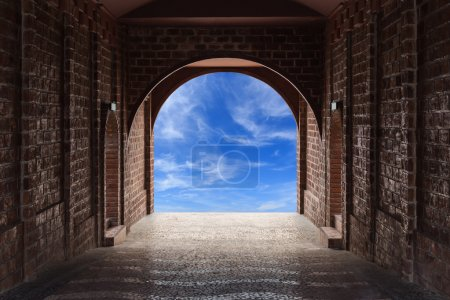 Walkway tunnel made by red brick and view of blue sky