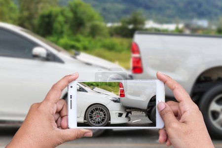Photo for Close up hand of woman holding smartphone and take photo of car accident - Royalty Free Image